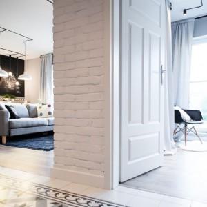 W przedpokoju na podłodze wyłożono wzorzyste płytki w iberyjskim stylu. Ściany wykończono taką samą cegłą jak ścianę w salonie. Projekt: Raca Architekci. Fot. Adam Ościłowski.
