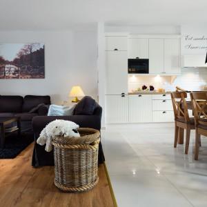 Otwarta na salon kuchnia stanowi serce domu. Właściciele chcieli przestrzeni z przytulnym klimatem, w której można spożywać rodzinne posiłki. Projekt: Małgorzata Błaszczak, Pracownia Mebli Vigo. Fot. Artur Krupa.