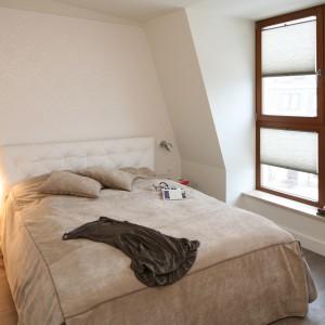 Beżowa narzuta oraz poduszki subtelnie ocieplają niewielką sypialnię. Efekt pogłębiają drewniane ramy okienne. Projekt: Małgorzata Borzyszkowska. Fot. Bartosz Jarosz.