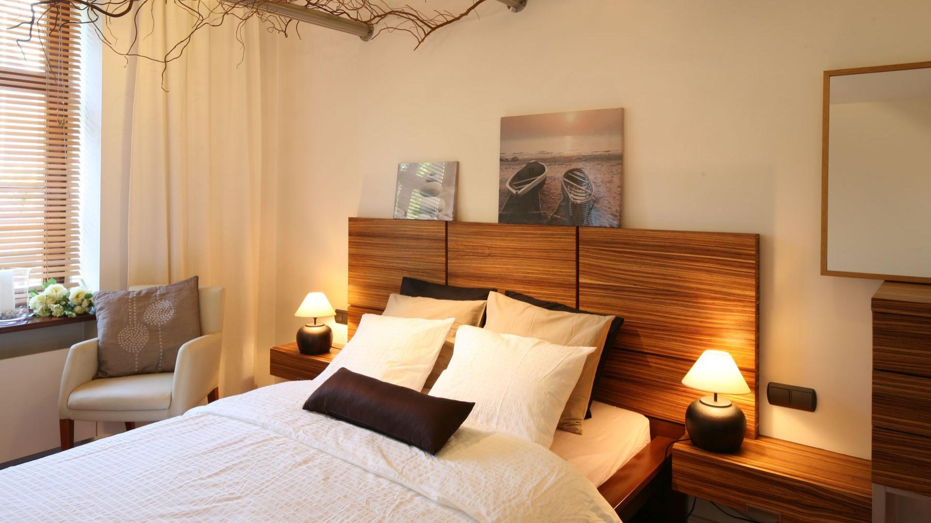 Ciepły klimat tej uroczej sypialni to niewątpliwie zasługa drewna. Występuje ono w postaci mebli, ale też dekoracji. Projekt: Urszula i Jakub Górscy. Fot. Bartosz Jarosz.