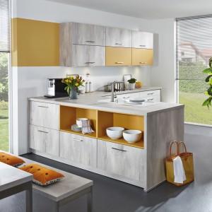 Jasne kolory drewna zestawiono z akcentami w kolorze ciepłej żółci. Półki po zewnętrznej stronie półwyspu częściowo otwarto i wykończono w żółtym kolorem. Fot. Brigitte.