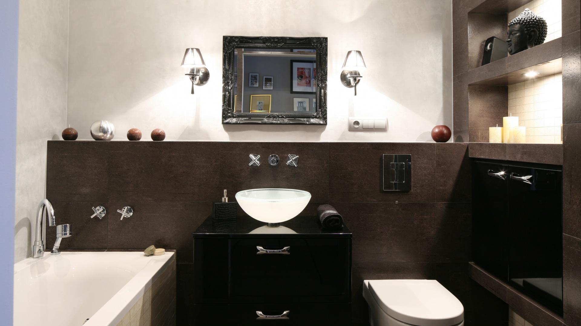 W łazience utrzymanej w stylu glamour po obu stronach lustra, na wysokości około 160 cm, umieszczono dekoracyjne kinkiety.  Łączą estetykę i funkcjonalność. Projekt: Joanna Nawrocka. Fot. Bartosz Jarosz.