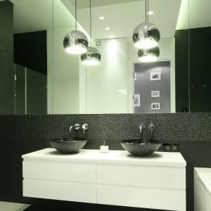 Nad umywalkami umieszczono dwie wiszące lampy, które zapewniają odpowiednie oświetlenie strefy lustra. Projekt: Agnieszka Ludwinowska. Fot. Bartosz Jarosz.