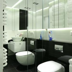 W wąskiej łazience najlepiej zastosować oszczędne, achromatyczne barwy, które dodadzą wnętrzu przestrzeni, a kontrastowe fragmenty poszerzą je wizualnie. Lustra zadziałają jak szkło powiększające. Projekt: Anna Maria Sokołowska. Fot. Bartosz Jarosz .