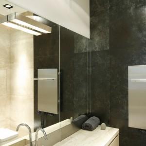 Do bardzo wąskiej łazienki wybrano materiały z połyskującą powierzchnią, natomiast prysznic od reszty łazienki oddziela jedynie tafla szkła, dzięki czemu łazienka wydaje się bardziej przestronna. Projekt: Izabela Mildner. Fot. Bartosz Jarosz.