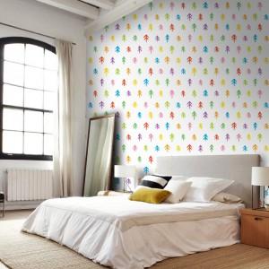 Kolorowe drzewka, wyglądające jakby narysowało je dziecko, zdobiące tapetę marki Picassi, wniosą do sypialni młodzieńczy urok. Fot. Picassi.