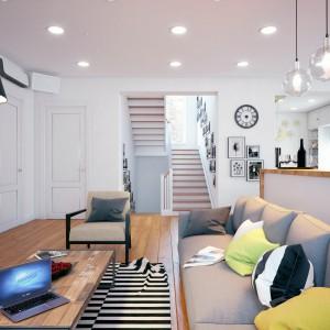 Biele, szarości i kolory naturalnego drewna, przełamane barwnymi detalami i czarnymi akcentami królują w strefie dziennej. Projekt i wizualizacje: Studio projektowe Geometrium.