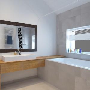 W łazience małżeńskiej dominują eleganckie szarości, ocieplone drewnianymi elementami i zaakcentowane czarnymi detalami. Geometryczne formy prezentują się nowocześnie i elegancko. Projekt i wizualizacje: Studio projektowe Geometrium.