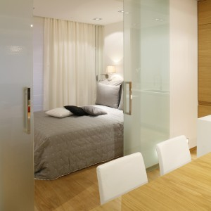 Sypialnię wyodrębniono z otwartej przestrzeni dziennej, ukrywając ją za szklanymi, przesuwnymi drzwiami. Projekt: Adam i Monika Bronikowscy. Fot. Bartosz Jarosz.