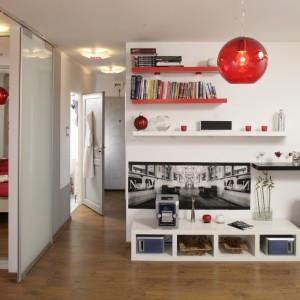Charakter niewielkiej sypialni podkreślają czerwone dodatki: pościel oraz mały stolik. Projekt: Magda Olszewska. Fot. Bartosz Jarosz.