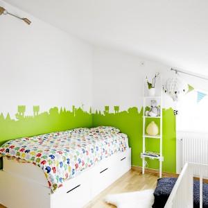 Na piętrze urządzono dwie sypialnie, w tym jedną dziecięcą. Paletę stonowanych barw, obecną w innych pomieszczeniach mieszkania, ożywiono soczystą, limonkową zielenią na ścianie, która układa się w fantazyjny krajobraz. Fot. Vastanhem.