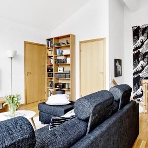 Hol drugiej kondygnacji przemieniono w urokliwy mały salonik z telewizorem i niewielką biblioteczką w rogu pomieszczenia. Fot. Vastanhem.