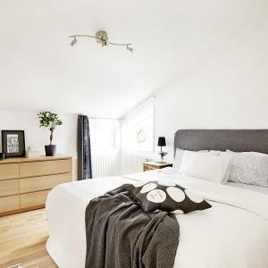 Sypialnia małżeńska to kontynuacja eleganckich barw ze strefy dziennej. Drewniana dębowa podłoga koresponduje z komodą pod skosem, a wokół łóżka stoją drewniane szafeczki nocne. Duże łóżko zdobi szary, tekstylny zagłówek. Fot. Vastanhem.