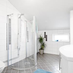 Łazienka z kabiną prysznicową na piętrze urządzona została w bieli, stonowanej delikatnie szarą podłogą. Fot. Vastanhem.