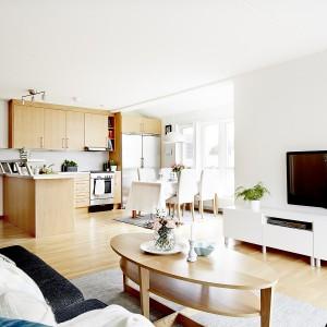 Centrum mieszkania jest otwarta strefa dzienna, w której urządzono przytulny salon i kuchnię z jadalnią, rozświetloną słońcem, wpadającym przez duże okna w wykuszu. Fot. Vastanhem.