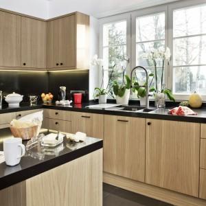 Meble kuchenne wykończone naturalnym, dębowym fornirem wieńczy czarny blat z konglomeratu kwarcowego. Ciepły kolor drewna, w połączeniu z okrągłymi, dekoracyjnymi uchwytami nadaje kuchni domową, przytulną atmosferę. Fot. Zajc Kuchnie, model Z5.