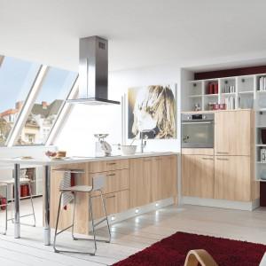 Fronty w jasnym kolorze drewna pięknie komponują się z białym blatem i białymi otwartymi półkami, stanowiącymi swoistą ramę dla zabudowy, w którą wpasowano piekarnik. Fot. Pinio, program PN100.