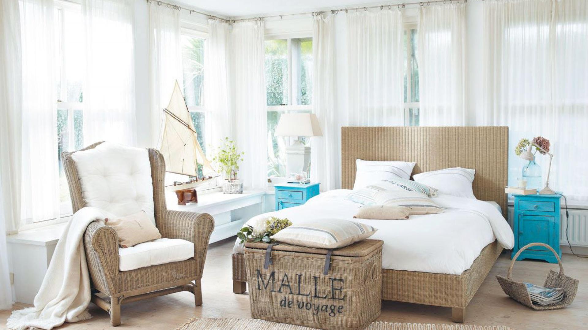 Białe wnętrze z dużymi oknami efektownie ocieplają meble z rattanu. Ciekawym urozmaiceniem aranżacji są turkusowe stoliki nocne w stylu retro. Lekkości dodają natomiast zwiewne firanki. Fot. Maison du Monde.