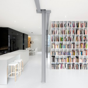 Ścianę w salonie, prostopadłą do wyspy kuchennej, pokrywa w całości obszerna, pojemna biblioteczka. Ustawione na niej książki, stają się barwnym akcentem w monochromatycznym wnętrzu. Projekt: Anne Sophie Goneau. Fot. Adrien Williams.