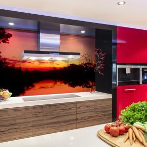 Nastrój w kuchni zbuduje fototapeta z pięknym widokiem na zachodzące nad jeziorem słońce. Pomarańczowy kolor wpadający w delikatny, pudrowy róż i czerwień harmonizuje z czerwonymi frontami mebli i ożywia przestrzeń. Tematyka fototapety uspokaja i relaksuje. Fot. Decomania.
