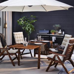 Stół z opuszczanym blatem Äpplarö w towarzystwie wygodnych krzeseł tworzy wygodne miejsce do odpoczynku na świeżym powietrzu. Zestaw dostępny w sklepach IKEA. Fot. IKEA.