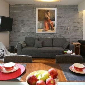 W niedużej kawalerce w szczególny sposób wyeksponowano ścianę za kanapą. Pokryta szarym beton eksponuje ekspresjonistyczny obraz. Projekt: Marcin Lewandowski. Fot. Bartosz Jarosz.