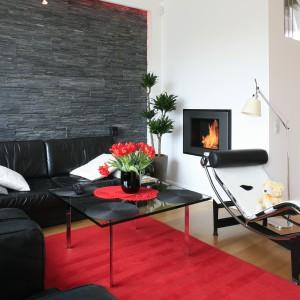 W minimalistycznym wnętrzu czerń, biel i czerwień wyznaczają ton całej aranżacji. Czarna ściana za kanapą została wyłożona dekoracyjnym łupkiem. Projekt: Michał Mikołajczak. Fot. Bartosz Jarosz.