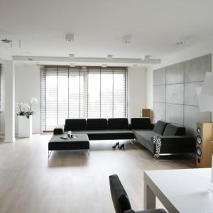 Przestronne wnętrze urządzono w minimalistycznym stylu. Stąd jedyną dekoracją wnętrza jest ściana za kanapą imitująca surowe betonowe płyty. Projekt: Agnieszka Ludwinowska. Fot. Bartosz Jarosz.