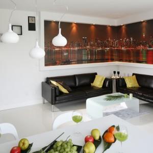 W skąpanym w bieli salonie czarne kanapy usytuowano na tle fototapety z panoramą Nowego Jorku. Projekt: Jolanta Kwilman. Fot. Bartosz Jarosz.
