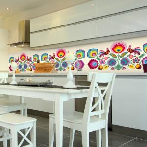 Ciekawym pomysłem jest ozdobienie ściany nad blatem fototapetą z folklorystycznym motywem. Feeria barw ożywia białą kuchnię a ludowy wzór koresponduje z klasycznymi meblami jadalnianymi. Fot. Livingstyle.