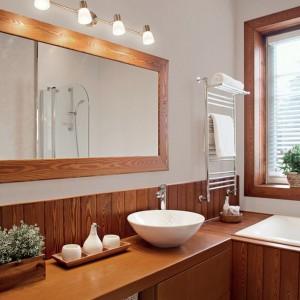 W łazience utrzymanej w klasycznych beżach i brązach ścianę nad drewnianą okładziną ścienną pomalowano na jasny odcień. Na zdjęciu: ściana pomalowana farbą marki Tikkurilla. Fot. Tikkurilla.
