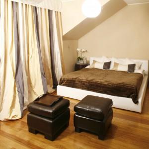 Przestronną sypialnię na poddaszu urządzono w ciepłych brązach i beżach, przez co wnętrze zyskuje przytulny klimat. Szyku dodają mu zamaszyste, ciężkie zasłony. Projekt: Joanna Liss. Fot. Bartosz Jarosz.