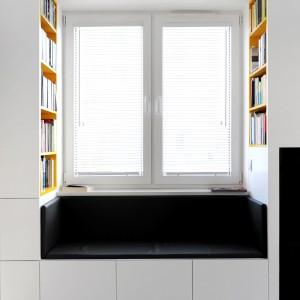 We wnęki okienne wpasowano siedziska, na których domownicy mogą usiąść i oddać się ulubionemu zajęciu - czytaniu książek przy najzdrowszym dla oczy, świetle dziennym. Książki są w zasięgu ręki, bo na półkach w zabudowie wokół okien. Projekt i zdjęcia: musk collective design.