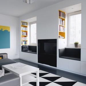 Przykuwającym wzrok elementem dekoracyjnym w salonie jest czarno-biały dywan z geometrycznym wzorem. Projekt i zdjęcia: musk collective design.