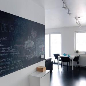 Praktyczny i modny dodatek w korytarzu stanowi farba tablicowa. Tutaj domownicy mogą zostawiać sobie notatki, wiadomości i sporządzać listę zakupów (np. nowych książek). Projekt i zdjęcia: musk collective design.