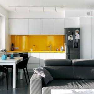 Ze względu na przyjęty styl życia domowników, nie było potrzeby urządzania dużej kuchni. Jednorzędowa zabudowa z wysokimi szafkami górnymi i sporym miejscem na przechowywanie okazała się wystarczająca. Wykonane z MDF-u białe fronty efektownie kontrastują z żółtą ścianą nad blatem i... samym blatem, który również ma oryginalny żółty kolor. Projekt i zdjęcia: musk collective design.