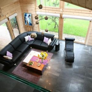 Minimalizm i prostota w zastosowanych rozwiązaniach i elementach wyposażenia sprawiają, że wszechobecne drewno nie przytłacza wnętrza. Pięknie łączy się z kanapą, oszczędnym w formie stolikiem i dekoracyjnym oświetleniem. A do tego salon, dzięki ogromnym przeszkleniom, otwiera się na otaczający dom krajobraz. Las dosłownie wnika do środka. Projekt: Tomasz Motylewski, Marek Bernatowicz. Fot. Bartosz Jarosz.