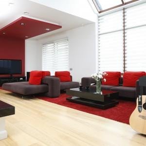 Przestronny salon urządzono w minimalistycznym duchu. Dominują tu proste formy oraz stonowane kolory, które ożywia czerwień. Projekt: Michał Mikołajczak. Fot. Bartosz Jarosz.