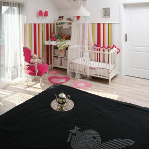 Oświetlenie sypialni w postaci eleganckiego żyrandolu okazało się niewystarczające dla dziecka. Dlatego przy łóżeczku zainstalowano kinkiety z kolorowymi kloszami. Fot. Bartosz Jarosz.