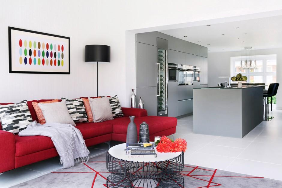 Po wyburzeniu ściany działowej, kuchnię otwarto na salon. Pomieszczenia spaja wizualnie szary kolor, w salonie dodatkowo ożywiony czerwonymi akcentami, ocieplającymi optycznie przestrzeń. Projekt: LLI Design. Fot. Zdjęcia: Alex Maguire Photography.