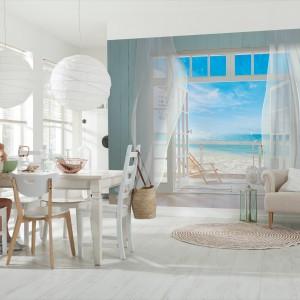 Fototapeta z motywem dużego okna, otwierającego się na malowniczy widok na błękitne niebo i piaszczystą plażę. Relaksuje domowników i dodaje świeżości pomieszczeniu. Fot. Decomania/Komar.