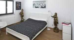 Biała, nowoczesna sypialnia przypomina galerię sztuki współczesnej. Wszystko za sprawą oryginalnych dekoracji.