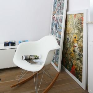 Designerski, biały fotel na drewnianych płozach, ustawiony w kącie sypialni, komponuje się z minimalistyczną aranżacją sypialni. Fot. Bartosz Jarosz.