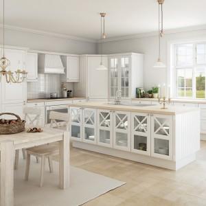 Klasyczna kuchnia z nieoczekiwanym rozwiązaniem - wyspą kuchenną z przeszklonymi drzwiczkami. Wzrok przykuwają dekoracyjne szprosy przecinające przeszklenia, za którymi wyeksponować można np. elegancką zastawę. Fot. Svane, model Stil Hvid.