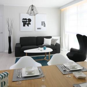 W niedużym salonie dominują jasne, stonowane barwy. Nieduża sofa w czarnym kolorze doskonale prezentuje się na ich tle. Projekt: Anna Maria Sokołowska. Fot. Bartosz Jarosz.