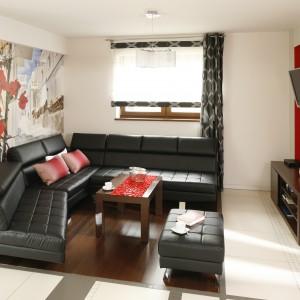 W salonie dominuje czerwień zdobiąca ściany. Na jej tle minimalistyczny czarny narożnik wykonany ze skóry prezentuje się niezwykle dostojnie. Projekt: Marta Kilan. Fot. Bartosz Jarosz.