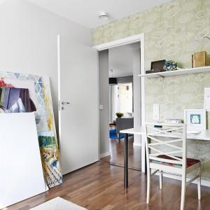 Jedna z sypialni została urządzona z myślą o artyście. Ścianę w pracowni wykończono tapetą z artystycznym motywem kwiatów w bladym odcieniu zieleni na nieco ciemniejszym tle. Fot. Vastanhem.