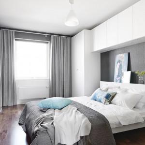 W jednej z sypialni postawiono na dominację szarości, jedynie delikatnie przełamanych bielą w postaci białej zabudowy wokół łóżka. Szare ściany i ciężkie zasłony w oknach nadają przestrzeni przytulny wyraz. Fot. Vastanhem.