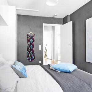 Ściana wykończona ciemnoszarą, satynową tapetą wizualnie stwarza wrażenie miękkości, co potęguje przytulny charakter pomieszczenia. Fot. Vastanhem.