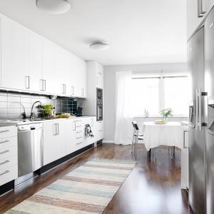 Białe meble kuchenne efektownie kontrastują z czarnymi, prostokątnymi poziomymi płytkami na ścianie. Zabudowę wykonała skandynawska firma Ballingslov, specjalizująca się w meblach na wymiar, wykonywanych z drewna. Fot. Vastanhem.